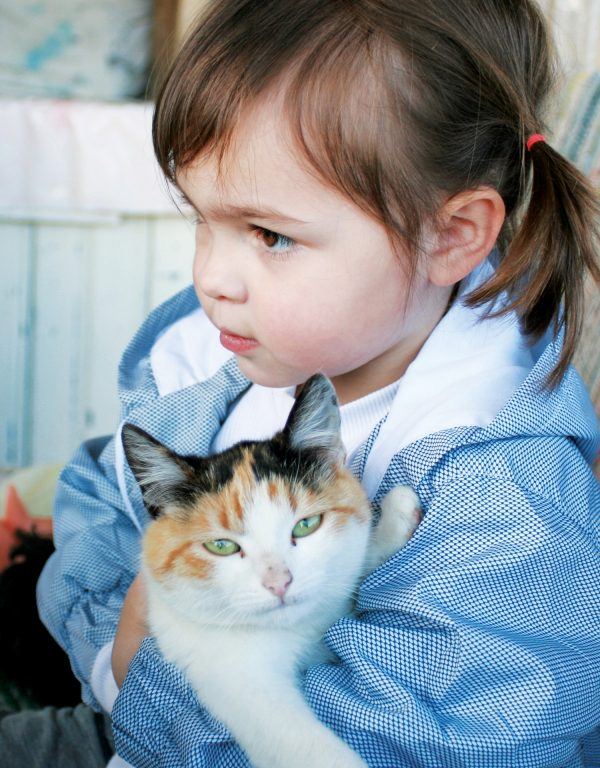 a cute girl wearing a blue jacket carrying her cat with green eyes