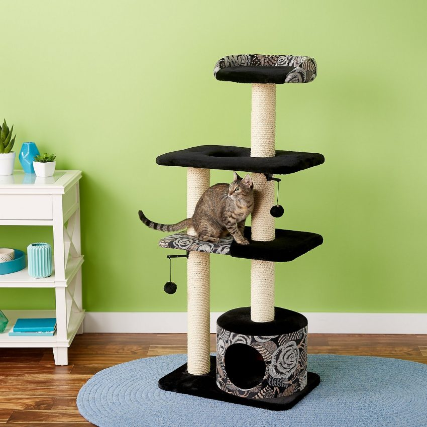 a very adorable black and white cat tree with a tiger cat on it