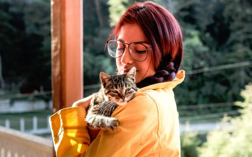 a cat lover lady with red hair embracing her tiger cat