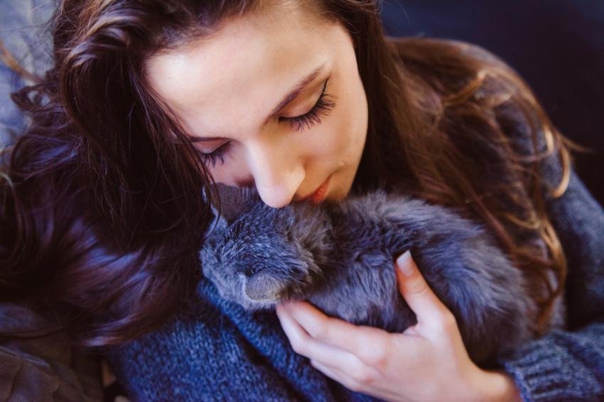 a lady hugging her little kitten