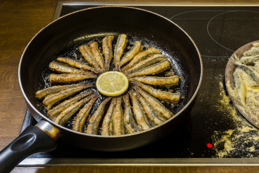 cooking anchovies with lemon on a pan