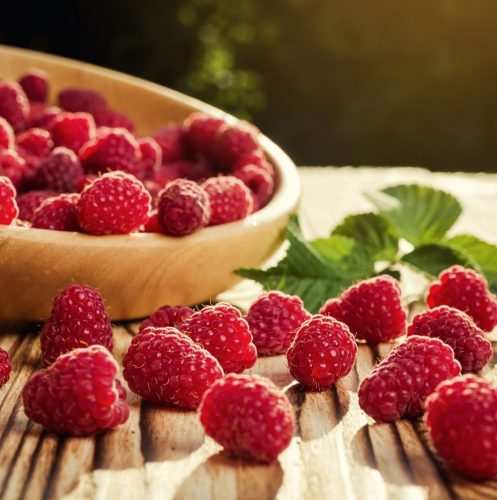 fresh raspberries on top of a wooden table and bowl